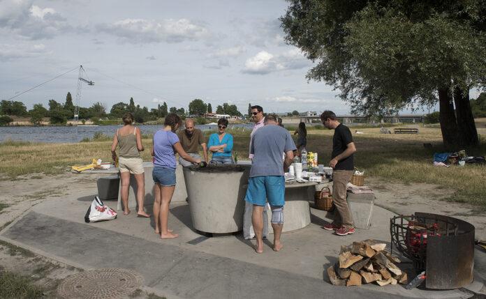 Symbolbild: Gruppe von Menschen steht um einen Grillplatz auf der Donauinsel. Bild: MA 45/WIENER WILDNIS.