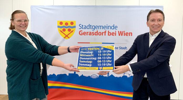 Bürgermeister Alexander Vojta und Stadtamtsdirektorin Gerda Hirschhofer präsentieren die neuen Öffnungszeiten im Gemeindezentrum Föhrenhain, Brünner Straße 62. Bild: Gemeinde Gerasdorf.