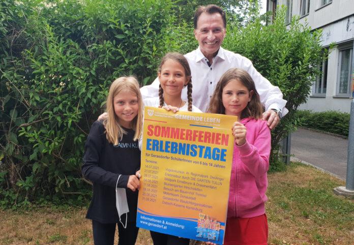 Bürgermeister Alexander Vojta präsentiert das Plakat der Sommerferien-Erlebnistage gemeinsam mit 3 Schülerinnen der Volksschule Oberlisse. Bild. Gemeinde Gerasdorf.