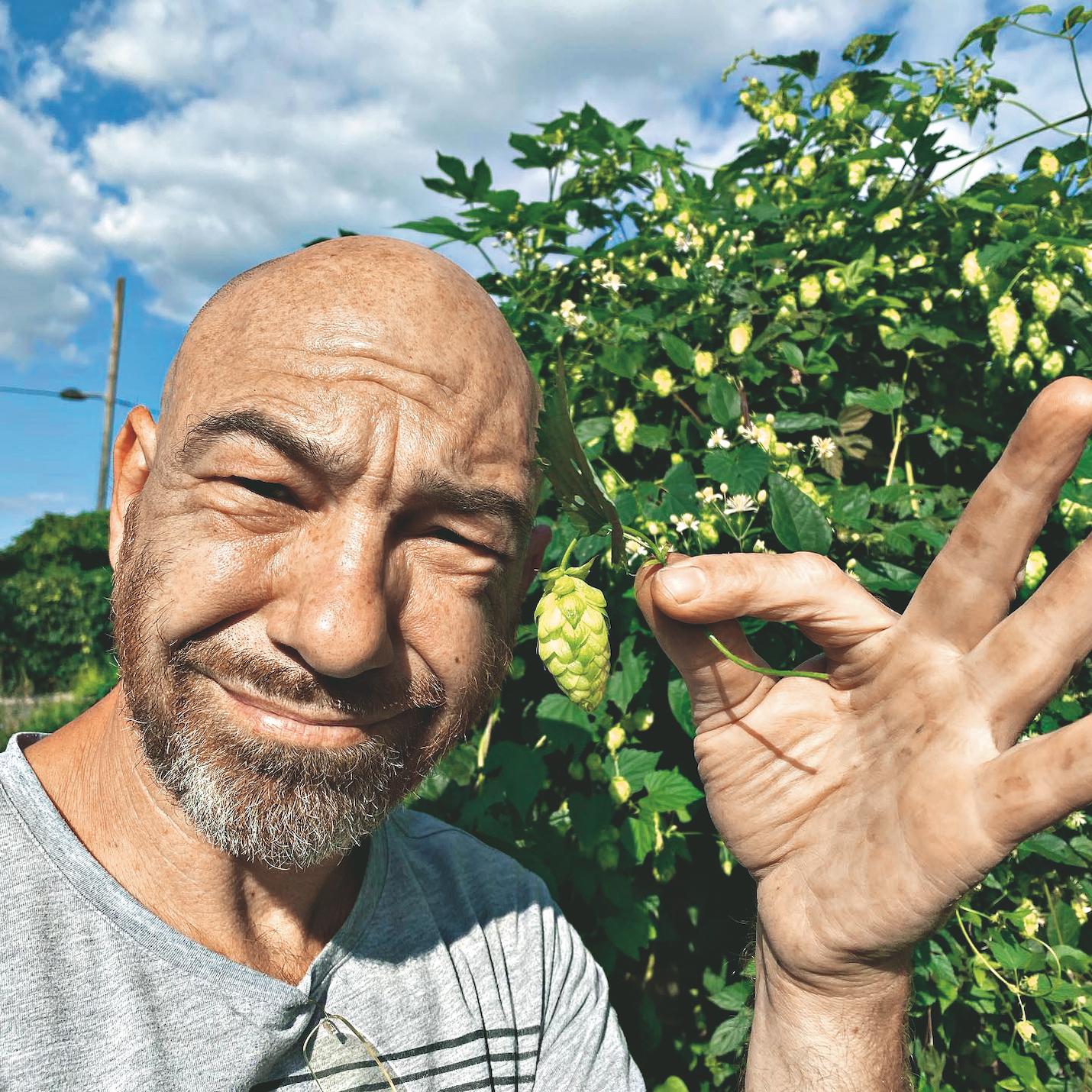 Roman Gregory mit Hopfen in seinem Garten. Bild: Privat.